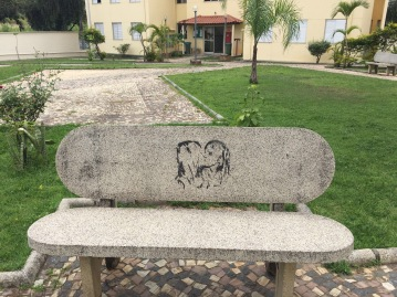 A bench in the open space between housing buildings.